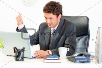 Angry  businessman sitting at office desk and menacingly brandishing his fist on laptop