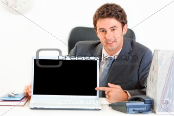 Smiling businessman sitting at office desk and pointing finger on laptop with blank screen
