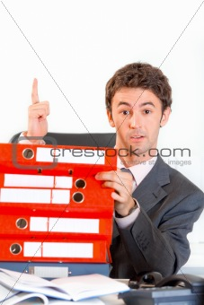 Sitting at office desk with pile of folders surprised businessman showing idea gesture