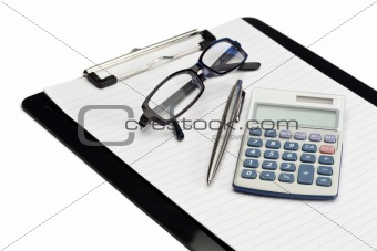 Angled note pad, pen, glasses and pocket calculator