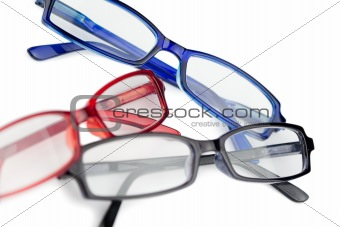 Three pairs of spectacles with blue red and black frames