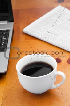 A cup of coffee with a laptop and a newspaper