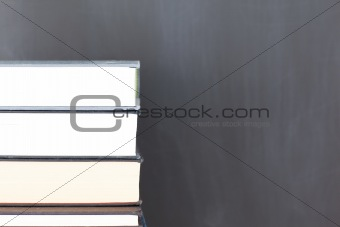 Stack of books and a clean blackboard