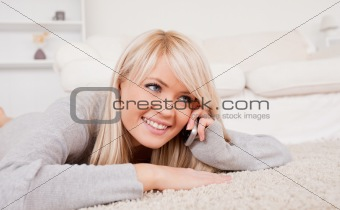 Attractive smiling blond woman talking on cell phone lying down