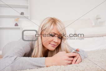 Attractive blond woman writing a text on cell phone lying down o