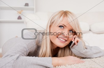 Beautiful happy blond woman talking on cell phone lying down on