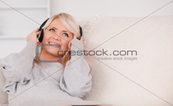 Beautiful blond woman with headphones lying in a sofa