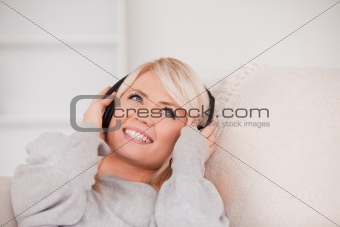 Charming young blond woman with headphones lying in a sofa