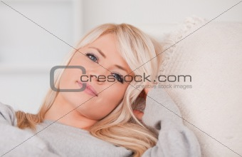 Portrait of a happy blonde woman lying on a sofa