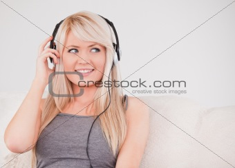 Beautiful young blond woman with headphones sitting in a sofa