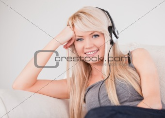 Attractive young blond woman with headphones sitting in a sofa