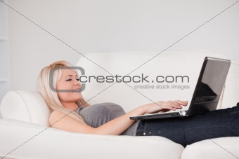 Beautiful woman relaxing on laptop lying on a sofa