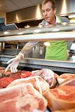 Market assistant picking meat