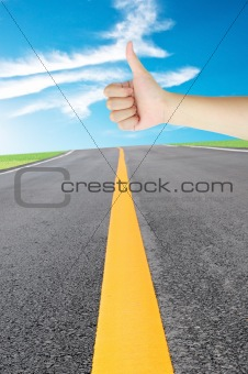 thumb up hand sign of woman for stops the car on the road under blue sky