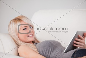 Charming woman lying on a sofa relaxing on a line of tablet comp