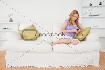 Beautiful red-haired woman writing a text message while sitting