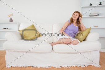 Beautiful red-haired woman on the phone sitting on a sofa