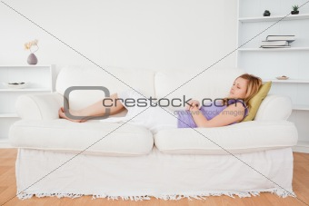 Beautiful woman taking a rest lying on a sofa