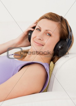 Attractive blond-haired woman listening to music lying on the so