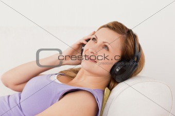 Smiling blond-haired woman listening to music lying on the sofa