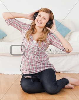 Blond-haired woman listening to music while sitting on the floor