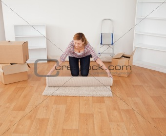 Blond-haired woman rolling up a carpet to prepare to move house