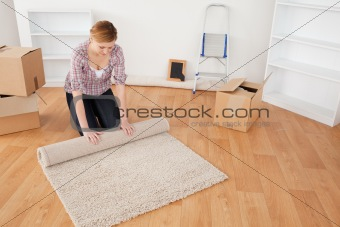 Cute woman rolling up a carpet to prepare to move house