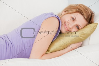 Attractive blonde woman resting while lying on the sofa