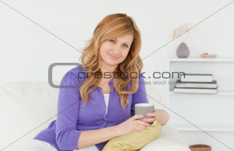 Attractive red-haired woman posing while sitting on a sofa