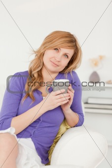 Attractive red-haired woman holding a cup of coffee while sittin