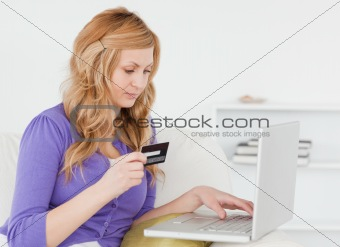Careful woman sitting on a sofa is going to make a payment on th