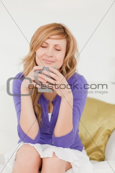 Beautiful red-haired woman holding and smelling a cup of coffee