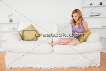 Beautiful red-haired woman sitting on a sofa and using a laptop