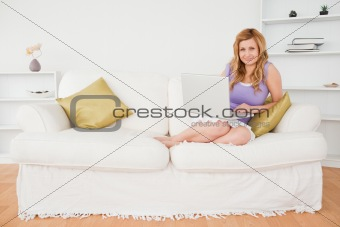 Beautiful red-haired woman using laptop and posing while sitting