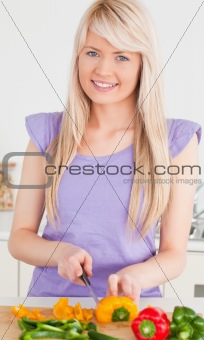 Smiling blonde female cutting peppers in modern kitchen interior