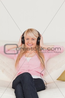 Attractive woman listening to music on her headphones while sitt