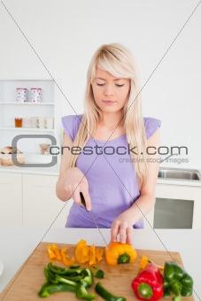 Beautiful blonde female cutting peppers in modern kitchen interi