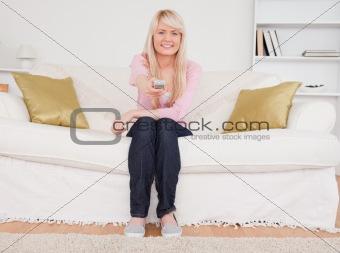 Beautiful blonde female posing while sitting on a sofa
