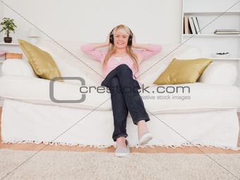 Beautiful blonde female listening to music on her headphones whi