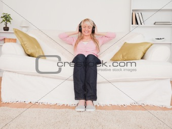 Beautiful blonde woman listening to music on her headphones whil