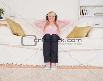 Attractive blonde female listening to music on her headphones wh