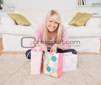 Smiling blonde woman sitting in the living-room with her shoppin