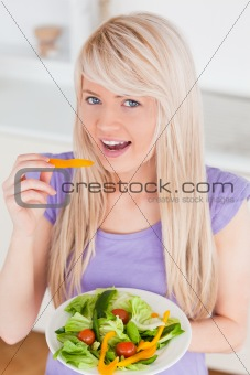 Beautiful smiling female eating her salad