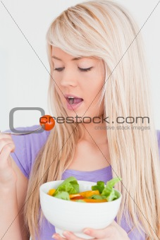 Beautiful smiling woman eating her salad