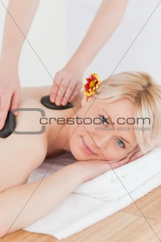 Attractive woman receiving a massage with hot stones
