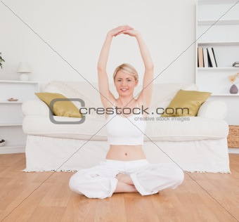 Blonde woman looking at the camera while doing fitness exercises