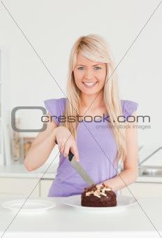 Beautiful blonde female cutting a cake in a plate