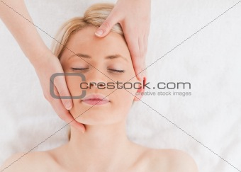 Cute young woman getting a massage on her face