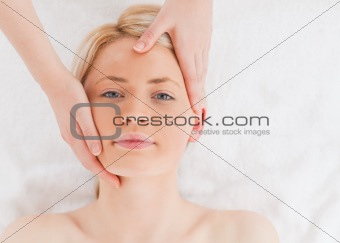 Blond-haired woman getting a massage on her face