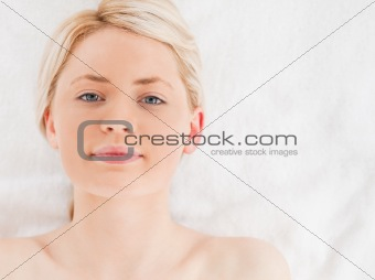 Attractive blond-haired woman looking at the camera while lying